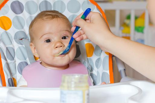 Baby eating food from a jar