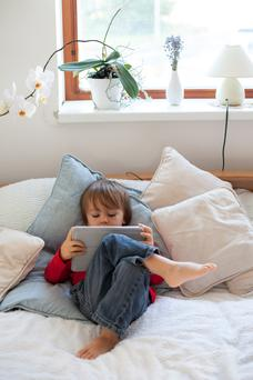 Be careful of letting children use screens in the evenings or close to bedtime. Stock image