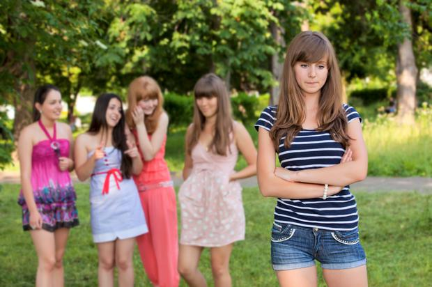 A group of girls teasing another girl