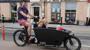 John Legge with his children Iseult (5) Aengus (3) and Odhran (18 months), who he cycles to school in a cargo bike in Dún Laoghaire. Photo: Arthur Carron