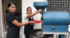 Karina Molina and Samira Guevara roasting coffee in Marcala, Honduras