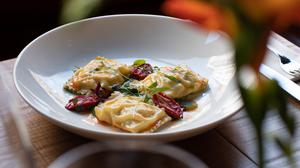 Ravioli filled with Dublin Bay prawns and lemon ricotta is accompanied by blobs of an asparagus and spinach puree and sweet sun-dried Datterini tomatoes