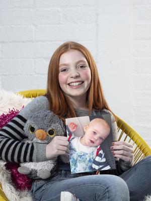 Lilly now, aged 10, and as a baby undergoing cancer treatment in the photo she is holding