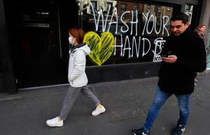 People pass graffiti reminding people to wash their hands on the window of a bar in Dublin's city centre. Photo: Brian Lawless/PA Wire