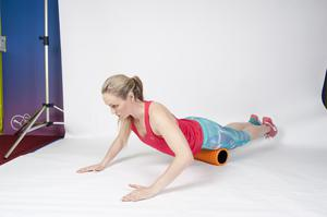 QUAD: 2/ Push down into a push-up and you will automatically allow the foam roller to move up and down the quad muscle at the front of the leg. Repeat numerous times.