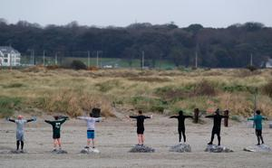 People adhere to social distancing guidelines as they take part in an exercise class on Dollymount Strand in Dublin. Photo: Brian Lawless/PA Wire