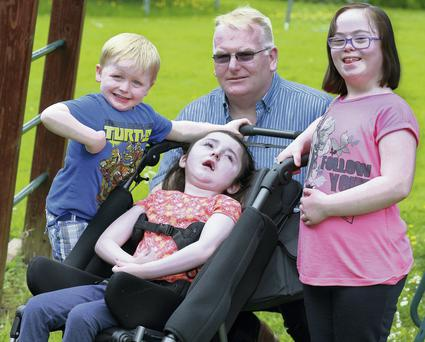 Gervin Kielt with his children, Daniel,3, Alicia, 10, and Caroline, 8, at home in their garden in Lusk. The family depends on the respite care provided to Alicia by the Children's Hospice, at LauraLynn House. Photo: Ronan Lang/Feature File