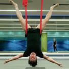 Journalist Joe O'Shea tries 'Antigravity Yoga' with the help of an instructor Esther at the Virgin Active Gym at the Broadgate Health Club in Central London.