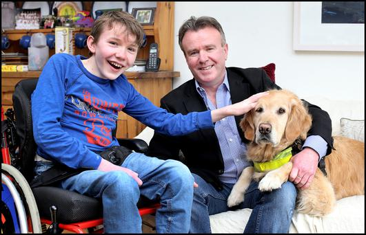 Tom Clonan with his son Eoghan, and Eoghan's assistance dog, Duke. Photo: Steve Humphries.