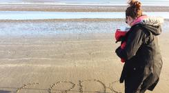 Imogen writes Conor's name in the sand. Photo: Imogen Carter