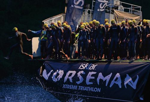 Athletes jump from a ferry into the Hardangerfjorden for the start of the 2013 Norseman Xtreme Triathlon in Eodfjord, Norway.