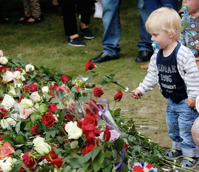 A child places a flower outside an Oslo cathedral on July 22, 2012. Thousands of Norwegians gathered at memorials to the 77 people killed a year earlier by Anders Breivik. REUTERS/Lise Aserud