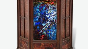 The stained-glass panel by Harry Clarke is housed in a mahogany and walnut inlaid cabinet