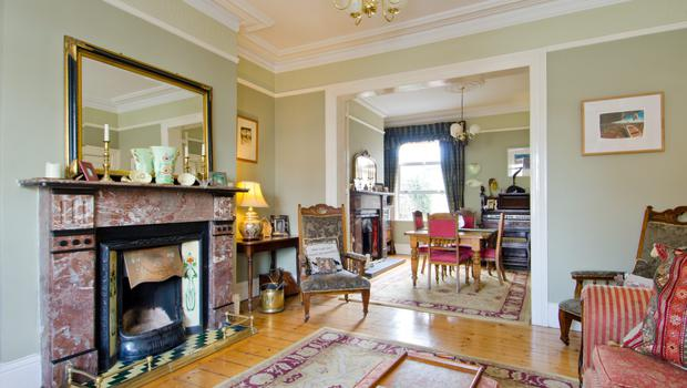 The drawing room, leading to the dining room, has matching marble fireplaces