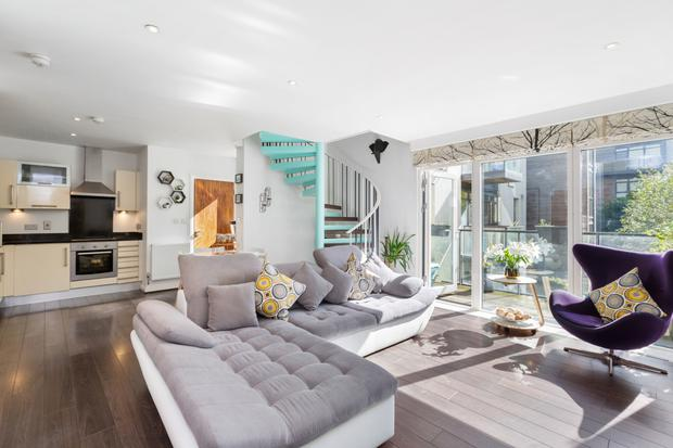 This apartment in Rialto has used bright colours and gloss units to bring the living space to life, and the corner sofa saves trying to squeeze in a full suite