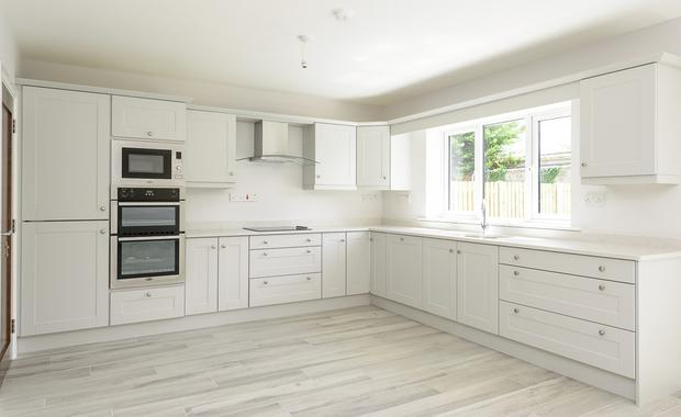 The contemporary shaker-style fitted kitchen comes with solid quartz worktops with upstands and soft-close doors and drawers