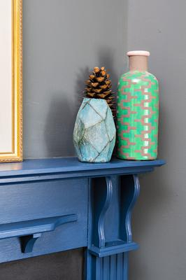 Some colourful pottery above the fireplace in the living room