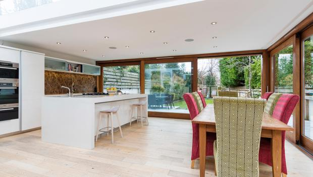 The kitchen and dining area of the large open-plan living space with floor-to-ceiling windows