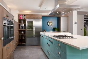 The kitchen with blue island unit and double hobs. Photo: Christian Haubold
