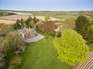 The property sits on 4.3 acres and includes a paddock and outbuildings