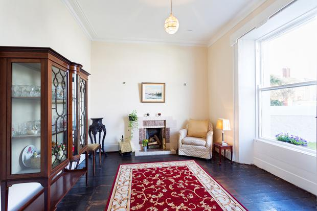 The sitting room with a timber floor and tiled fireplace.