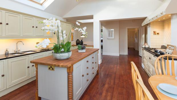 The extension features a kitchen with large wooden island unit, a large cream Aga with two gas-fired ovens and one electric oven, and four Velux windows