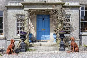 Dogs and urns flank the front door
