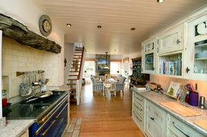 The kitchen has distressed-effect cabinets and a rangestyle cooker
