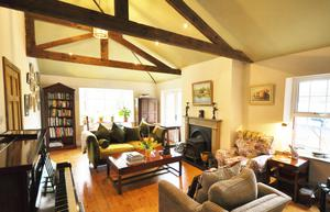 The sitting room has a vaulted ceiling and a bay window with seat