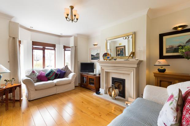 The living room at the front of No17 Elton Court has a bay window and sandstone fireplace