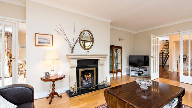 The lounge has a wooden floor, open fire and double doors to the garden