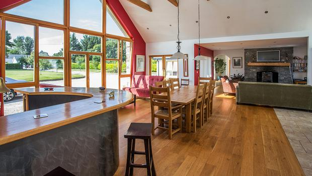Open-plan living/kitchen/dining room with double-height ceiling