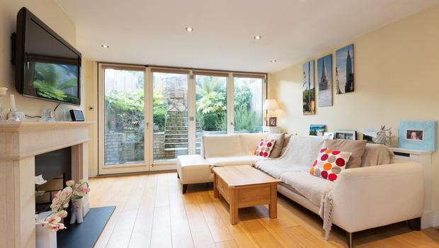The living room has a timber floor and doors out to the garden