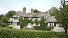 The residence's character features tall chimneys and original lead-paned windows.