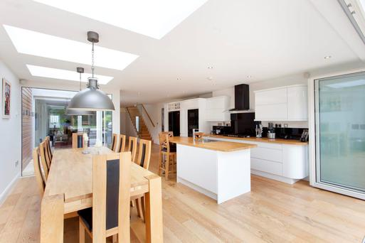 The bespoke spacious kitchen is fitted with high gloss units and a centre island