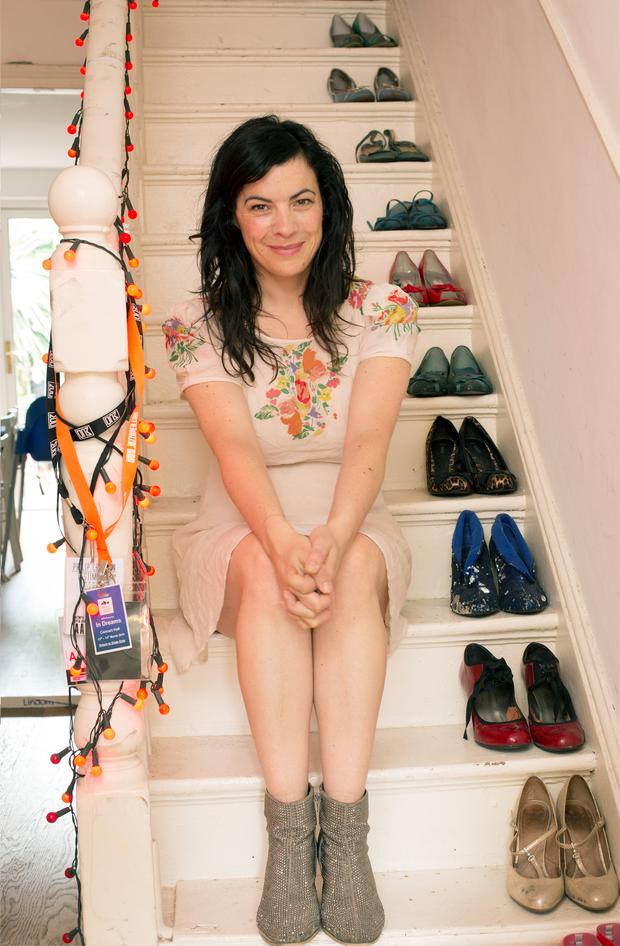 Camille on the steps of her stairs, decorated with her collection of shoes, which often play a part in her performances