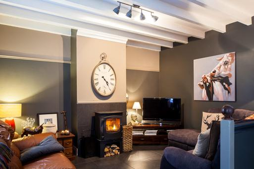 Living room with painted ceiling beams and solid-fuel stove.