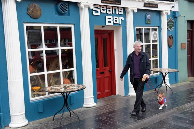 A local and his pet stroll past Seans bar, which boasts a documented history dating back to 900AD.