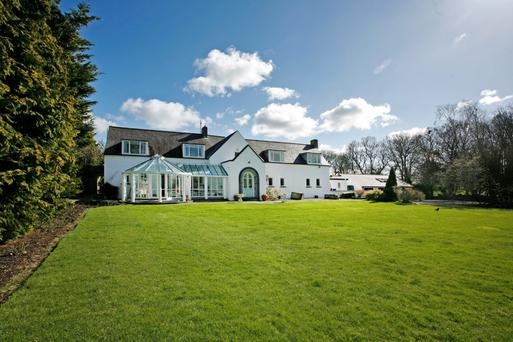 The house is on three acres of grounds which include a tennis court and paddocks.