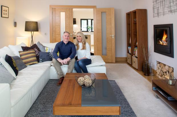 Fergal Doyle and his wife Kim Mackenzie in their sitting room which is accessed through double doors from the kitchen. The stove, which is set into the wall, is wood-burning. The leather unit is from BoConcept. Photo: Tony Gavin.