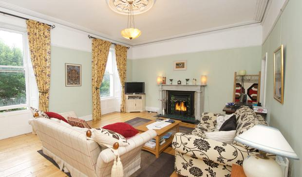 The large living room on the first floor has a marble fireplace and other period features.