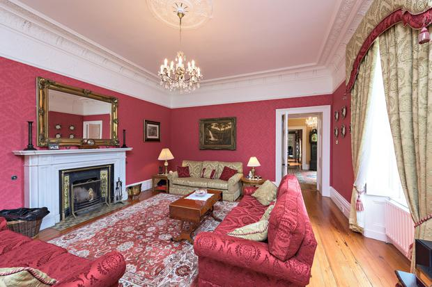The formal drawing room with a marble fireplace.