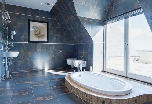The sunken bath in the master ensuite bathroom with views of the garden.
