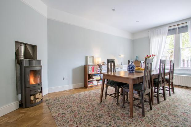 The living room features an imported Danish Pejse wood-burning stove.