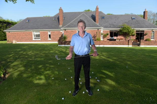 Eamonn Coghlan practises his golf swing on the lawn outside his home in Porterstown. Photo: Bryan Meade.