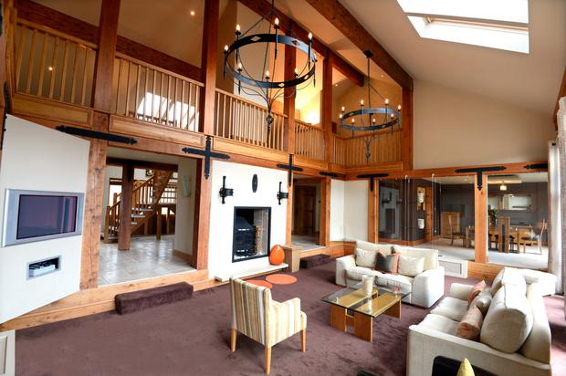 The gallery landing overlooks the grand living room, which has a fully glazed wall into the dining room.