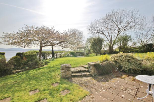 The patio with lawn and gazebo beyond.