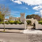 This two-storey home with a 19th century turret has ample living space and gardens.