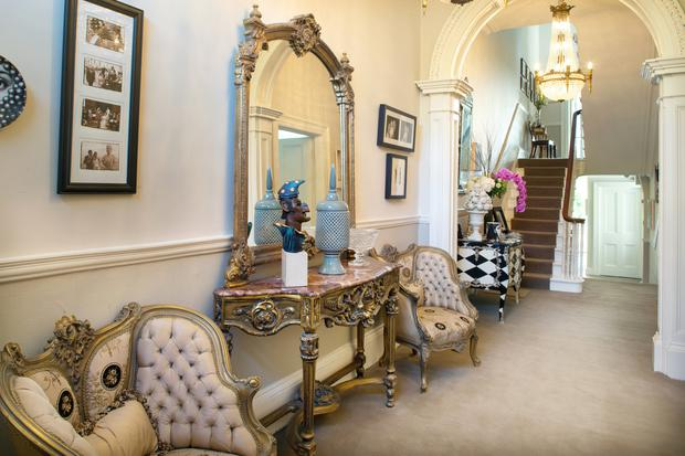 The hall is home to a marble and gilt console table with matching mirror. The armchairs are covered in silk, and other details include the Mr Punch sculpture by Graham Knuttel.