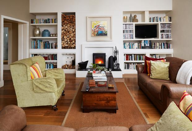 The living room with glossy walnut floor, fireplace and log store.
